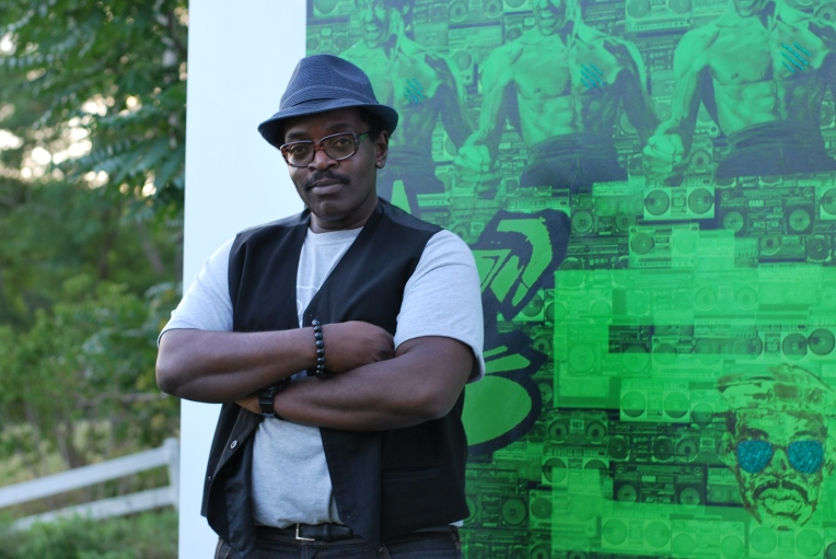 Fab 5 Freddy posing in front one of his works