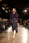 Aubergine hooded duster belted over a black knit dress.